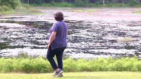 Jeune femme marchant près d'un lac banque de vidéos