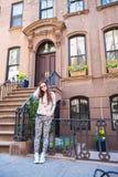 Jeune femme marchant près de vieilles maisons dans historique Photographie stock libre de droits