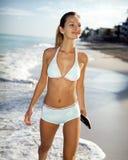 Jeune femme marchant sur la plage Photos libres de droits