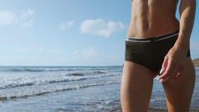 Jeune femme marchant sur la plage banque de vidéos