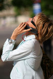 Jeune femme marchant sur la rue et parlant au téléphone Photos stock