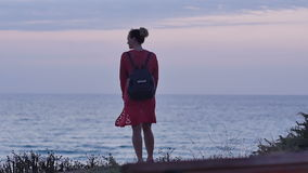 Jeune femme marchant sur le bord de la mer au crépuscule clips vidéos