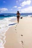 Jeune femme marchant sur le bord de la mer sur le sable Photo stock