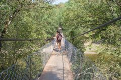 Jeune femme marchant sur le pont suspendu au-dessus de la rivière Image stock