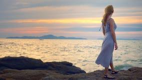 Jeune femme marchant sur un rocheux et appréciant la vue du coucher du soleil, éclaboussant des vagues banque de vidéos