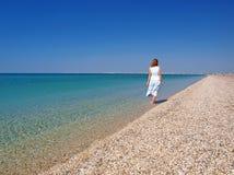 Jeune femme marchant sur une plage Photos stock