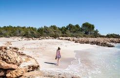 Jeune femme marchant sur une plage blanche idyllique de sable sur la côte méditerranéenne images libres de droits