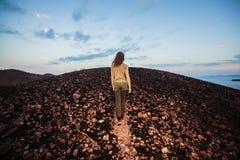 Jeune femme marchant vers le haut d'une colline Images stock