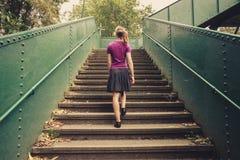 Jeune femme marchant vers le haut des escaliers Images libres de droits