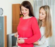 Jeune femme mesurant la taille de l'ami Photographie stock