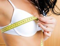 Jeune femme mesurant son sein à la maison Photo stock