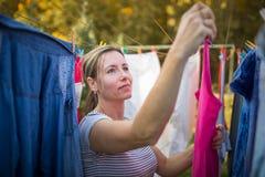 Jeune femme mettant la blanchisserie sur une corde dans son jardin images libres de droits