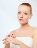 Jeune femme mettant la crème sur sa main Photo stock