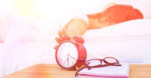 Jeune femme mettant son réveil pendant le matin photo libre de droits