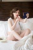 Jeune femme mettant sur le baume à lèvres photo stock