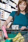 Jeune femme mettant un paquet dans un chariot à achats Image stock