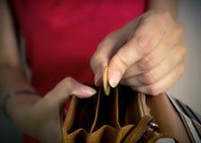 Jeune femme mettant une pièce de monnaie dans une bourse Images stock