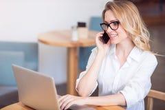 Jeune femme mignonne à l'aide de l'ordinateur portable et du téléphone images stock