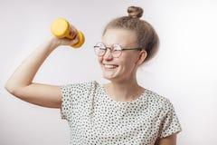 Jeune femme mignonne attirante riant et tenant le dumbell Projectile de studio photographie stock
