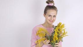 Jeune femme mignonne avec les fleurs jaunes de mimosa banque de vidéos