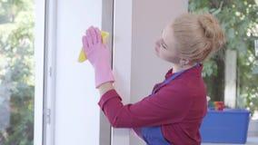 Jeune femme mignonne ayant la fenêtre de nettoyage d'amusement avec du chiffon de fenêtre Service des travaux domestiques et de n banque de vidéos