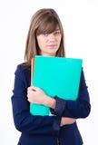Jeune femme mignonne d'affaires dans une jupe avec des dépliants verts et oranges dans des mains semblant avant direct Photographie stock libre de droits