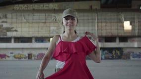 Jeune femme mignonne dans l'uniforme militaire essayant sur la robe rouge et dansant autour, souriant dans le bâtiment abandonné  clips vidéos