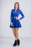 Jeune femme mignonne dans la robe de bleu marine sur le fond blanc Image stock