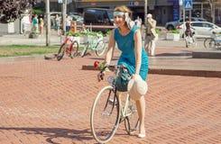 Jeune femme mignonne dans la robe de vintage faisant un cycle sur la rue pendant le festival en Europe Photos libres de droits