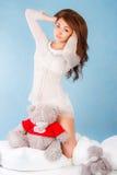 Jeune femme mignonne dans un lit avec un ours de nounours Photographie stock libre de droits