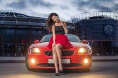 Jeune femme mignonne de brune s'asseyant sur un capot de voiture rouge de luxe de cabriolet au coucher du soleil images stock