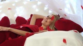 Jeune femme mignonne dormant dans le lit et se réveiller répandu avec des pétales des roses rouges banque de vidéos