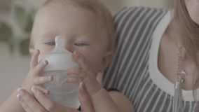 Jeune femme mignonne en gros plan alimentant son bébé du petit biberon dans la cuisine Concept d'une famille heureuse banque de vidéos