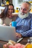 Jeune femme mignonne et homme supérieur regardant l'écran du filet Photo stock