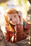 Jeune femme mignonne gaie positive posant près de l'arbre en parc Photographie stock libre de droits