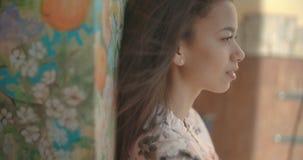 Jeune femme mignonne posant au-dessus de la belle peinture murale banque de vidéos
