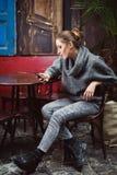 Jeune femme mignonne regardant dans son smartphone se reposant en café Photos stock