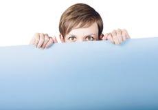 Jeune femme mignonne se cachant derrière le panneau d'affichage de promo Photo libre de droits