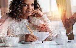 Jeune femme mignonne souriant tout en écrivant l'information importante dans son carnet photographie stock libre de droits