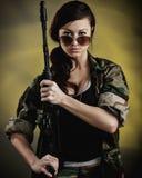 Jeune femme militarisée avec le fusil d'assaut Image stock