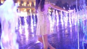 Jeune femme mince dans des danses de robe dans la fontaine lumineuse le soir, tir de mouvement lent banque de vidéos