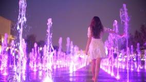 Jeune femme mince dans des promenades de robe dans la fontaine le soir, tir de mouvement lent banque de vidéos