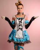 Jeune femme mince dans la robe érotique Alice au pays des merveilles sur un fond rose Photos stock
