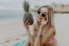 Jeune femme mince dans le bikini et des lunettes de soleil tenant l'ananas frais sur la plage de mer photographie stock