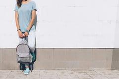Jeune femme mince dans les jeans et le T-shirt se tenant contre W blanc Photo stock