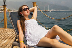 Jeune femme mince dans un bain de soleil blanc photo libre de droits