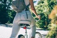 Jeune femme mince dans un T-shirt blanc, jeans et avec un sac à dos s Photo stock