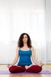 Jeune femme mince de brune en position de lotus avec des yeux fermés Photographie stock libre de droits