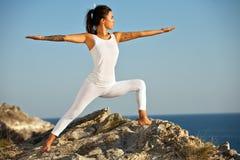 Jeune femme mince de yoga dans le zen méditant dans la pose de guerrier détendant dehors sur les montagnes et la mer sur le lever Image libre de droits