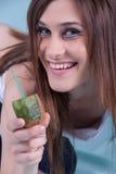 Jeune femme mince en bonne santé, tenant une paille dans le kiwi Photo libre de droits